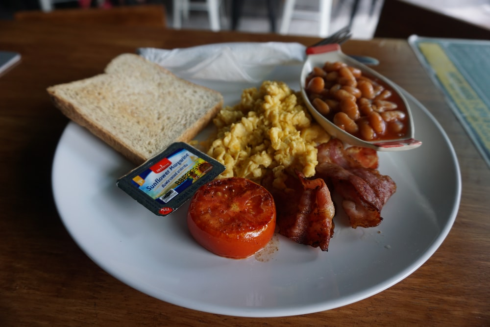 plate of breakfast meal with beans, scrambled egg, bacon and slice of bread