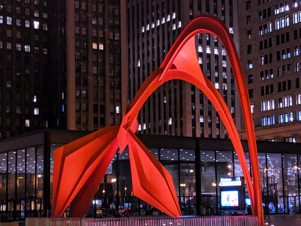 red abstract sculpture near building during night