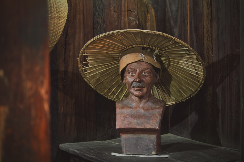brown bust with brown round hat