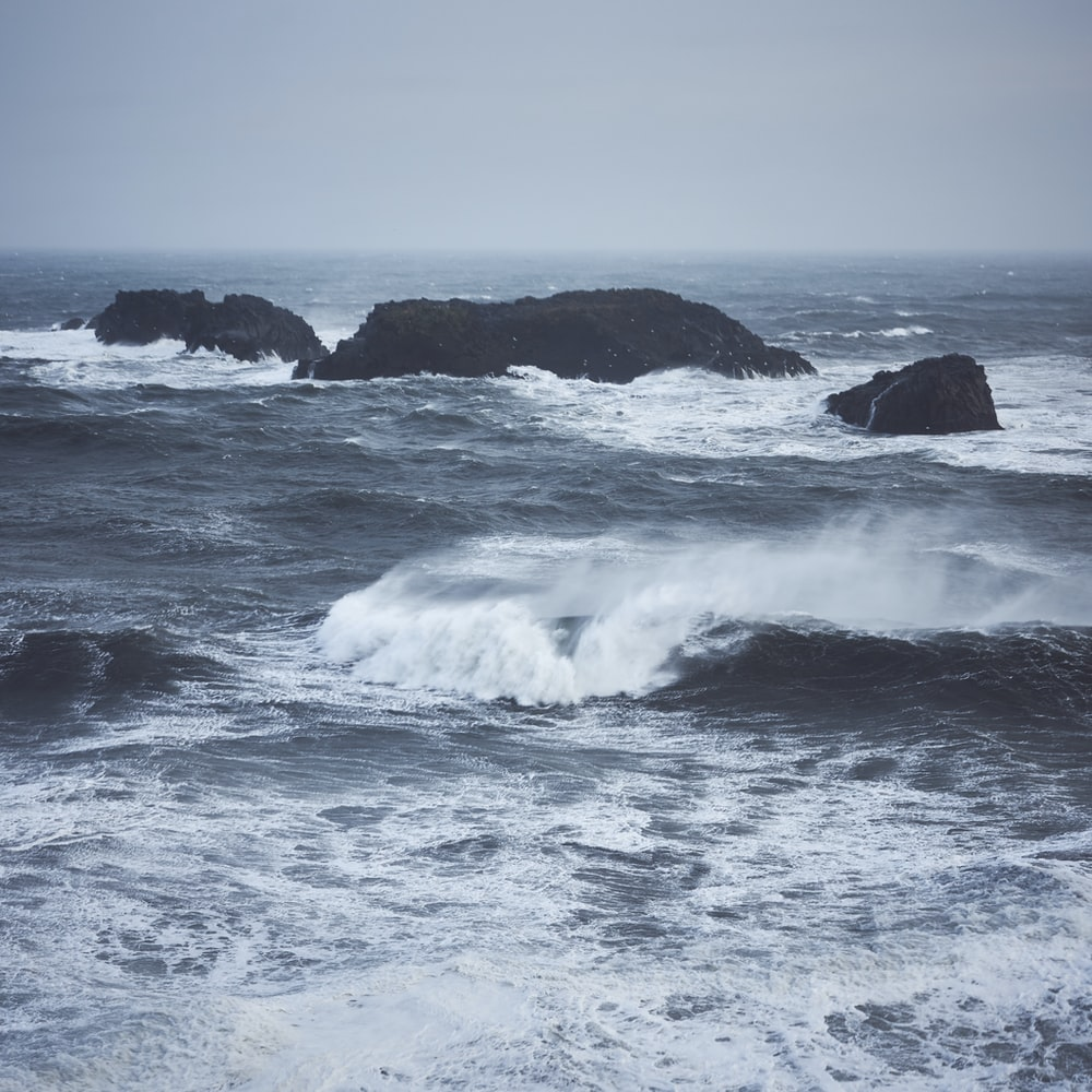 crashing waves and rocky islands during day