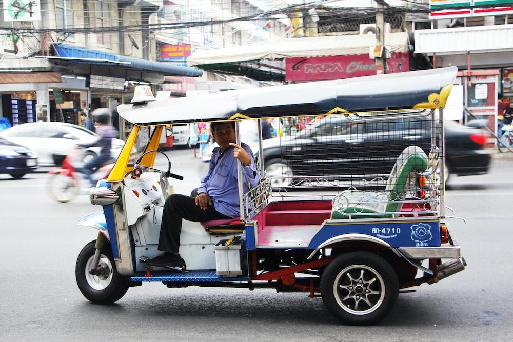 man driving multicolored 3-wheel vehicle