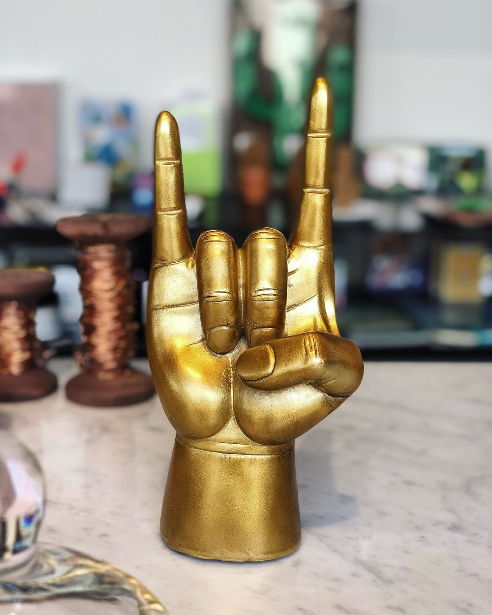 brass-colored rock and roll hand sign decor
