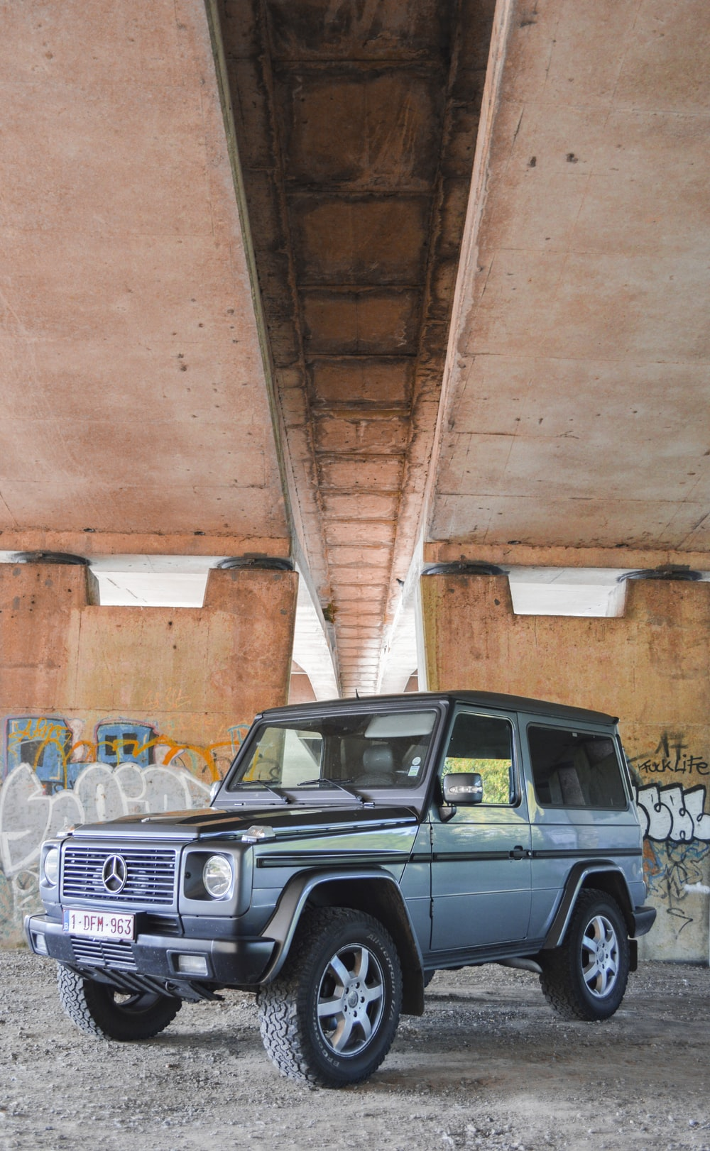 blue and black Mercedes-Benz SUV under bridge during daytime