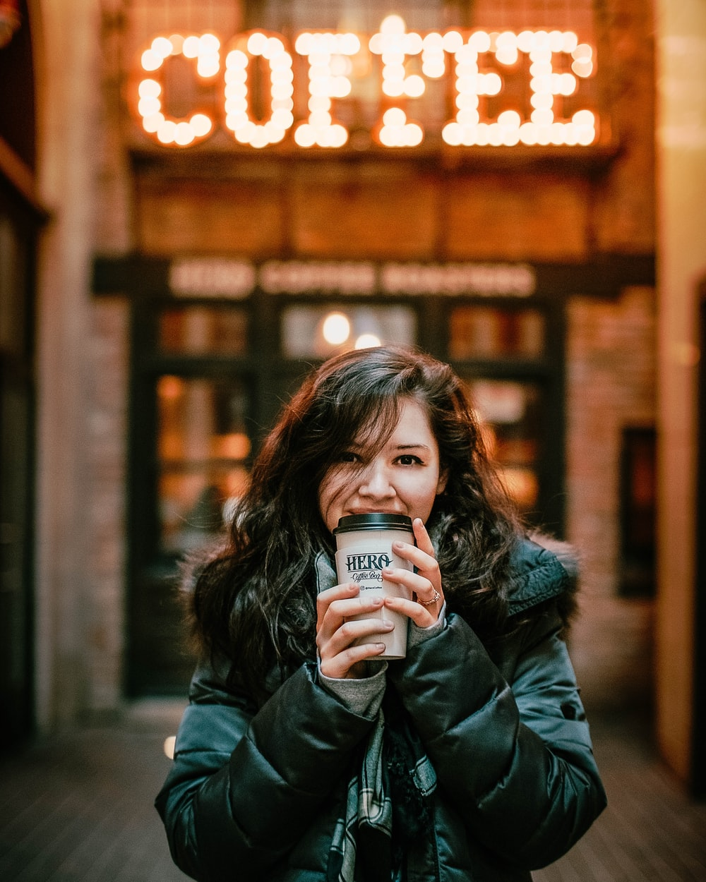 woman holding hot beverage outside coffee shop