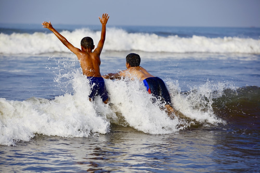 two boys playing with the waves