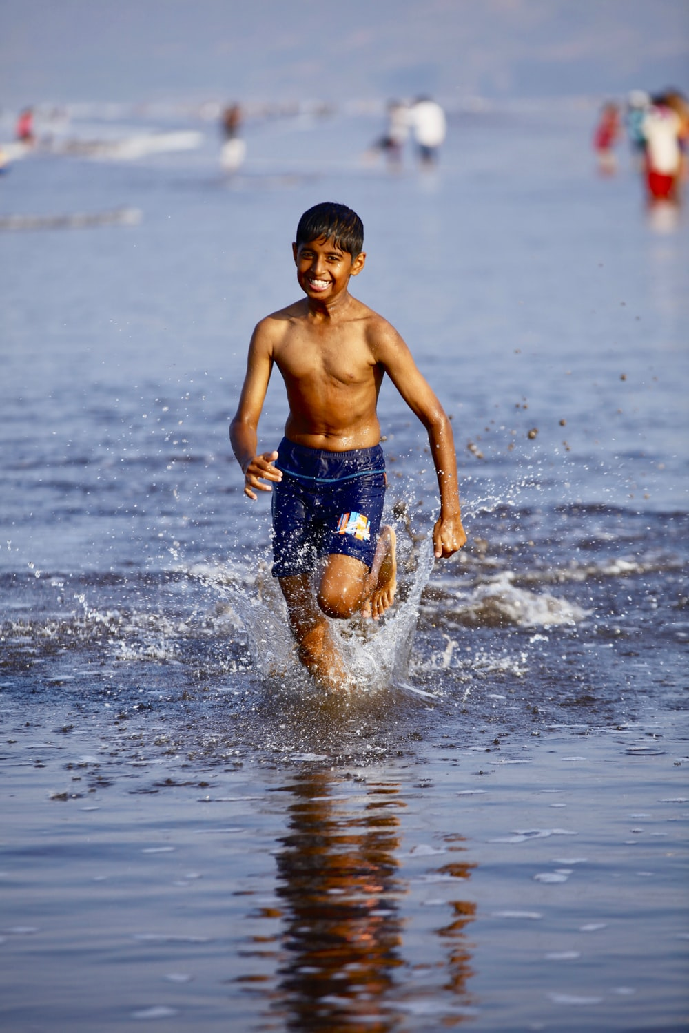 boys in blue shorts running in water