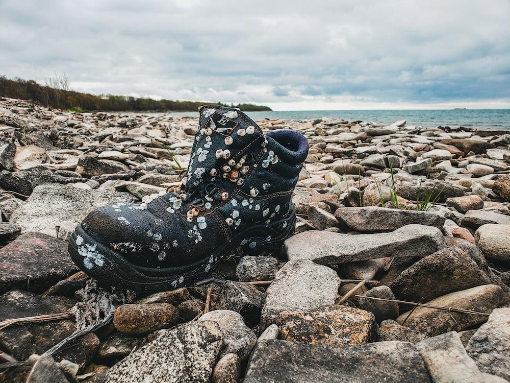 unpaired black boot on rocks