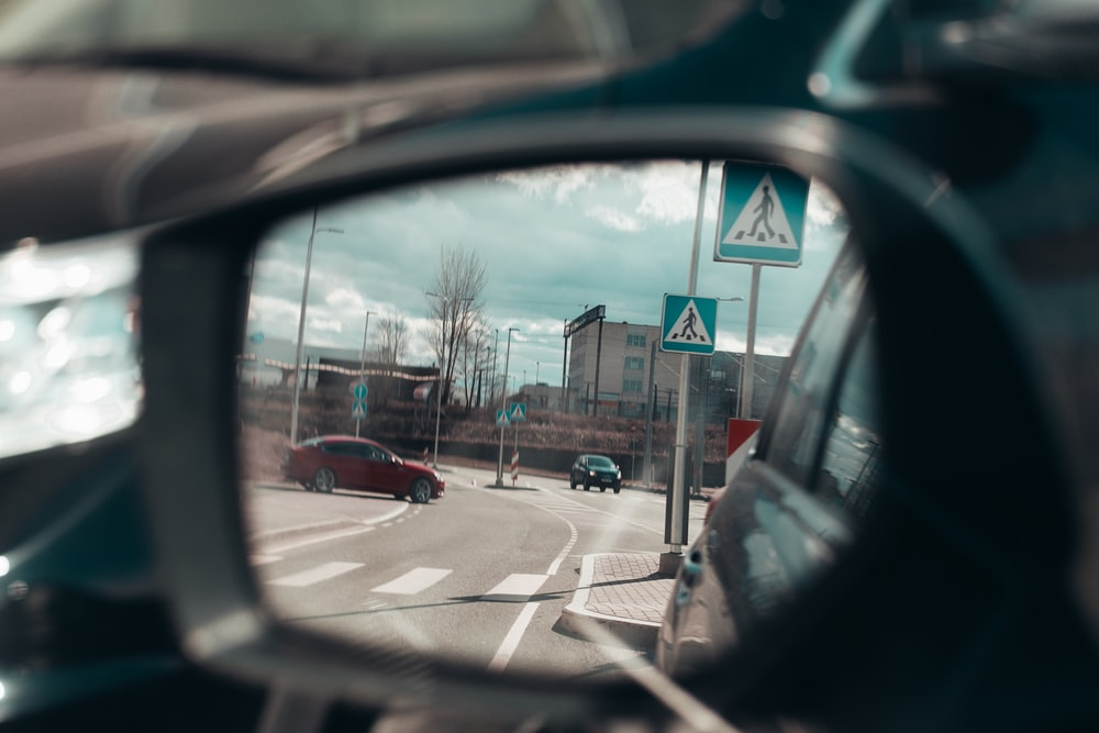 vehicle side mirror viewing red vehicle on road