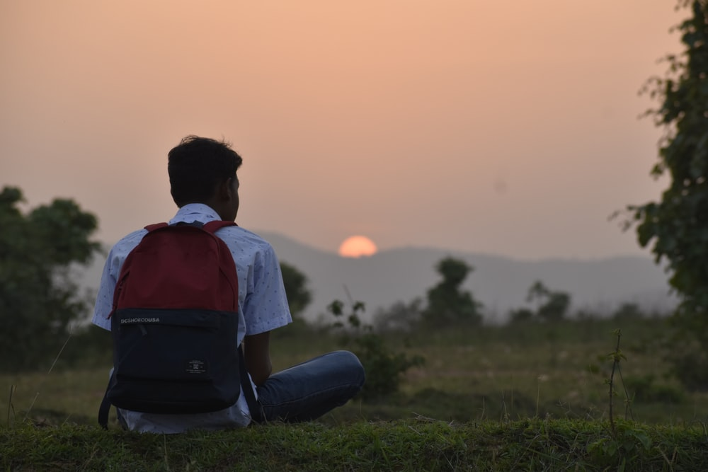 man wearing backpack sitting on grasses