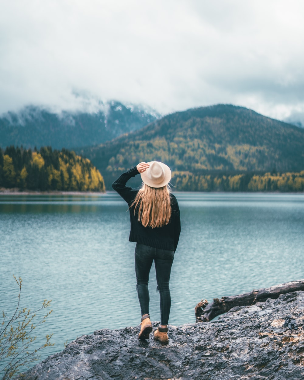woman in white hat, black jacket, and blue jeans standing near body of water
