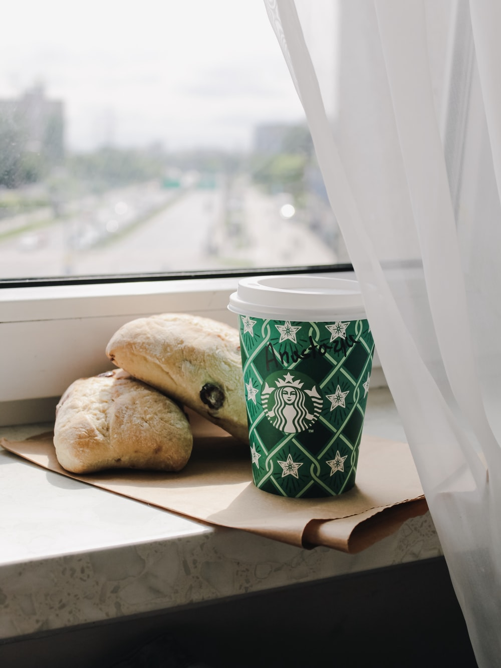 green Starbucks disposable cup near two breads
