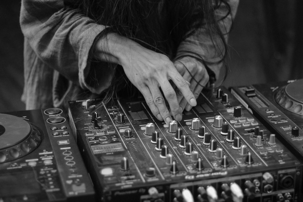 grayscale photo of person operating audio mixer