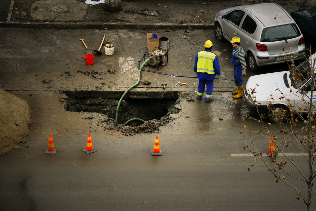 Construction workers draining a hole in the street