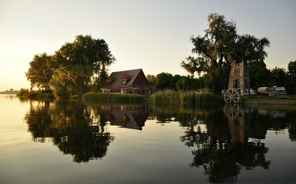 house near body of water during golden hour