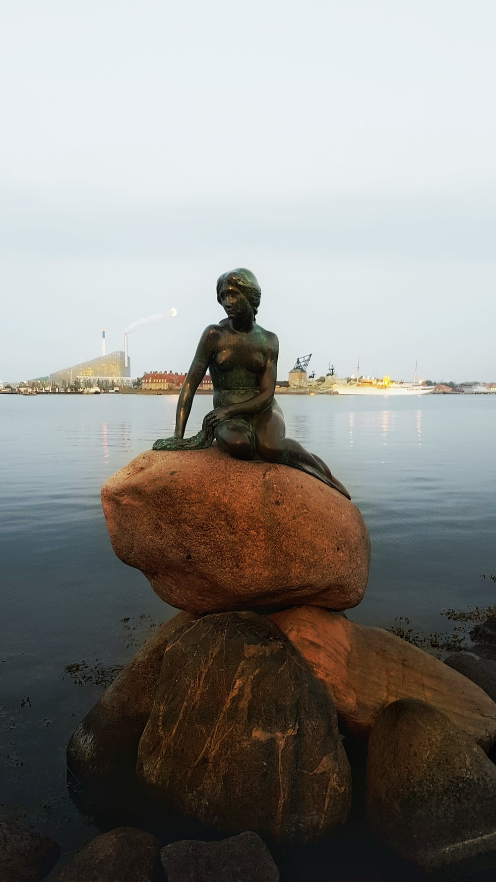 female statue on rock during daytime