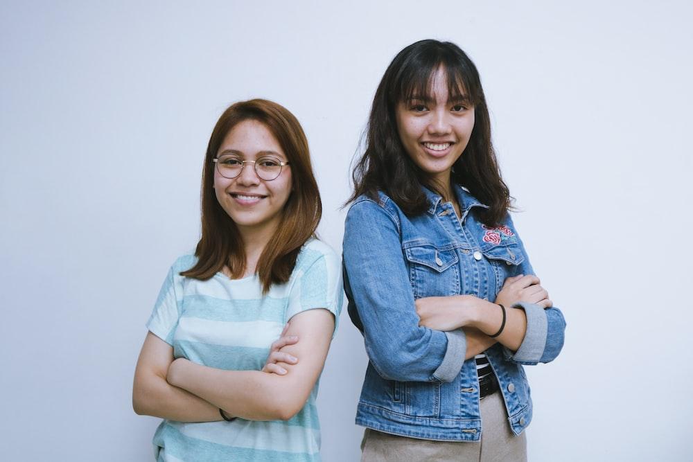 two woman beside wall