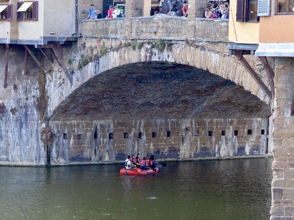 persons on boat underneath bridge