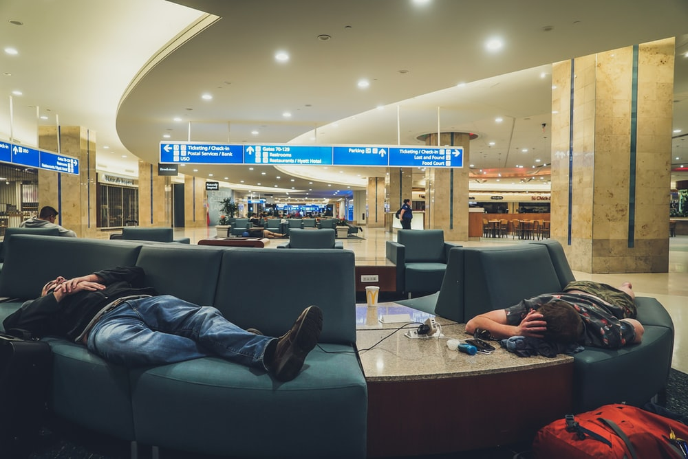 two person sleeping on blue leather sofa inside concrete building