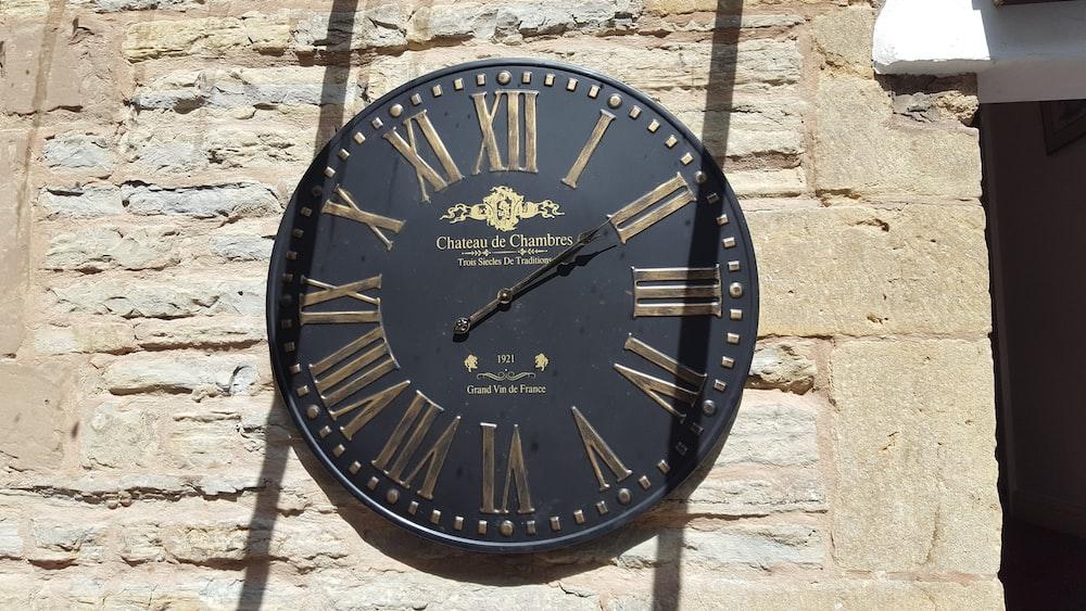 round black and brown analog wall clock displaying 2:10