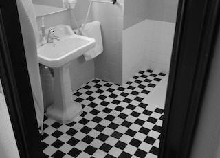 grayscale photo od white pedestal sink