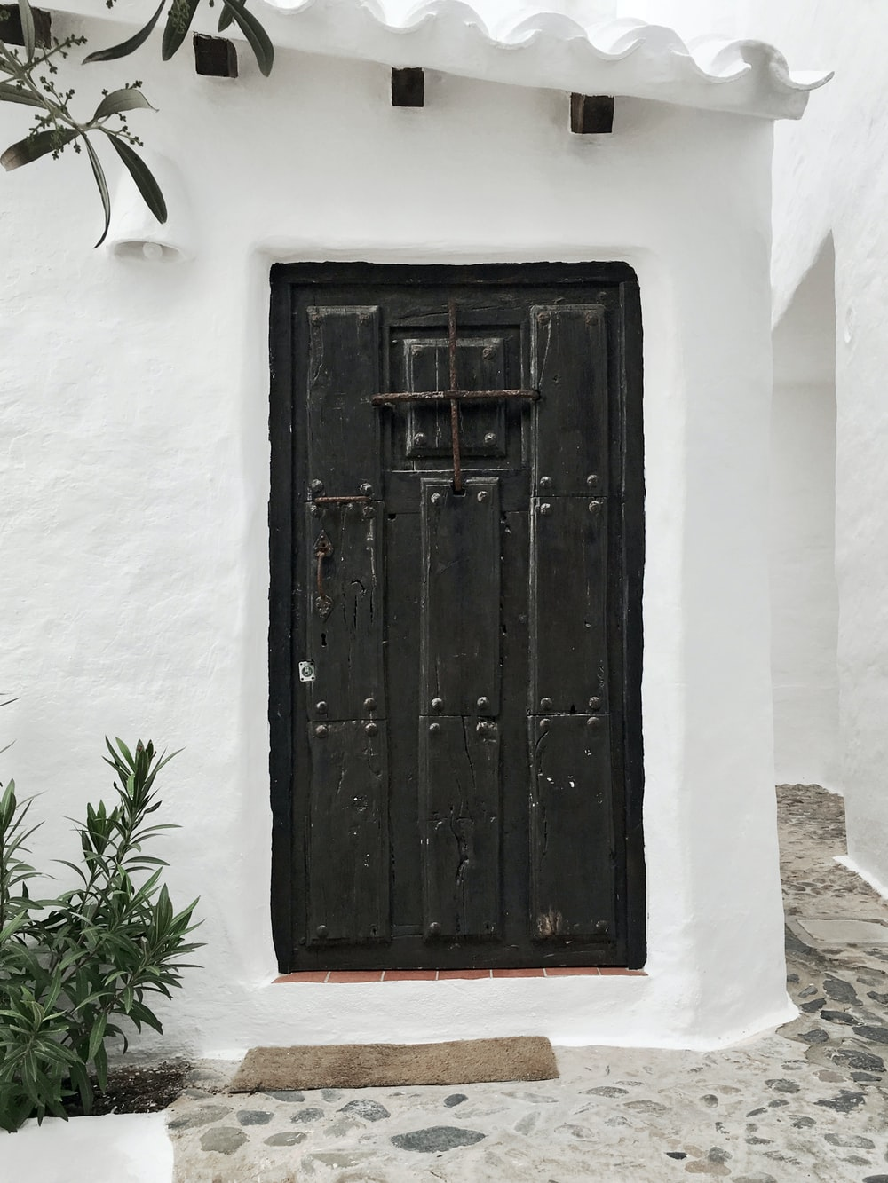 white building with closed black wooden door