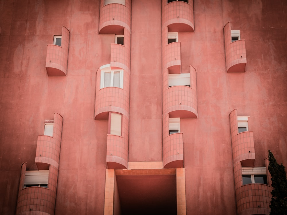 pink concrete building with balconies and windows