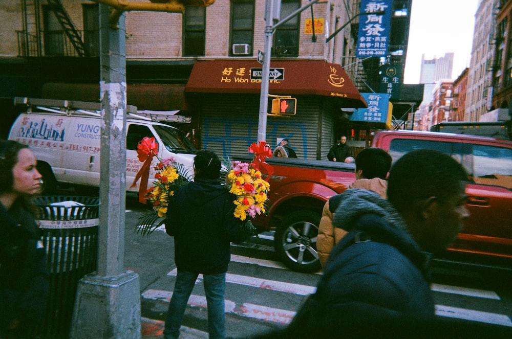 person holding flowers near pedestrian
