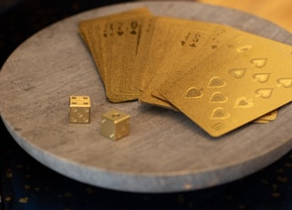 gold cards and two dices on round wooden platform