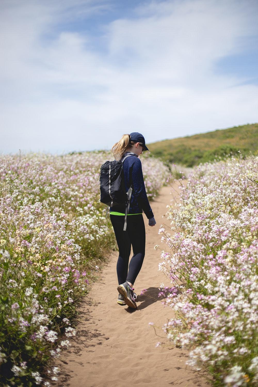 woman walking between flower fields