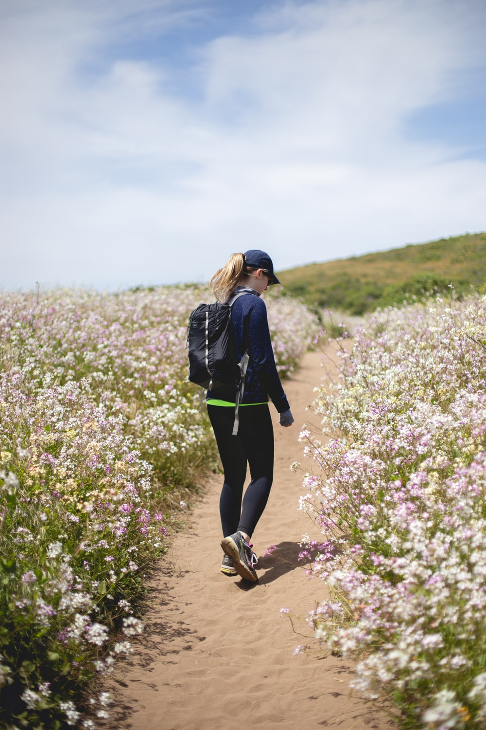 woman walking between flower fields