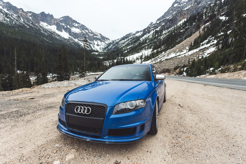 blue Audi car near road