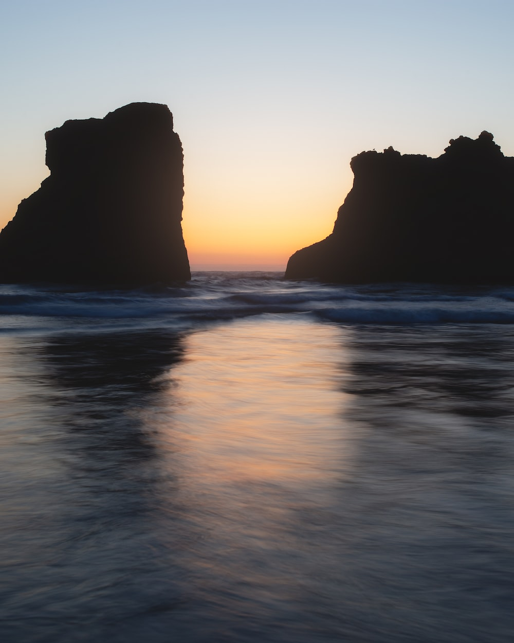 rock formation in body of water during golden hour