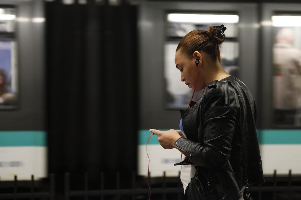 woman using phone near train