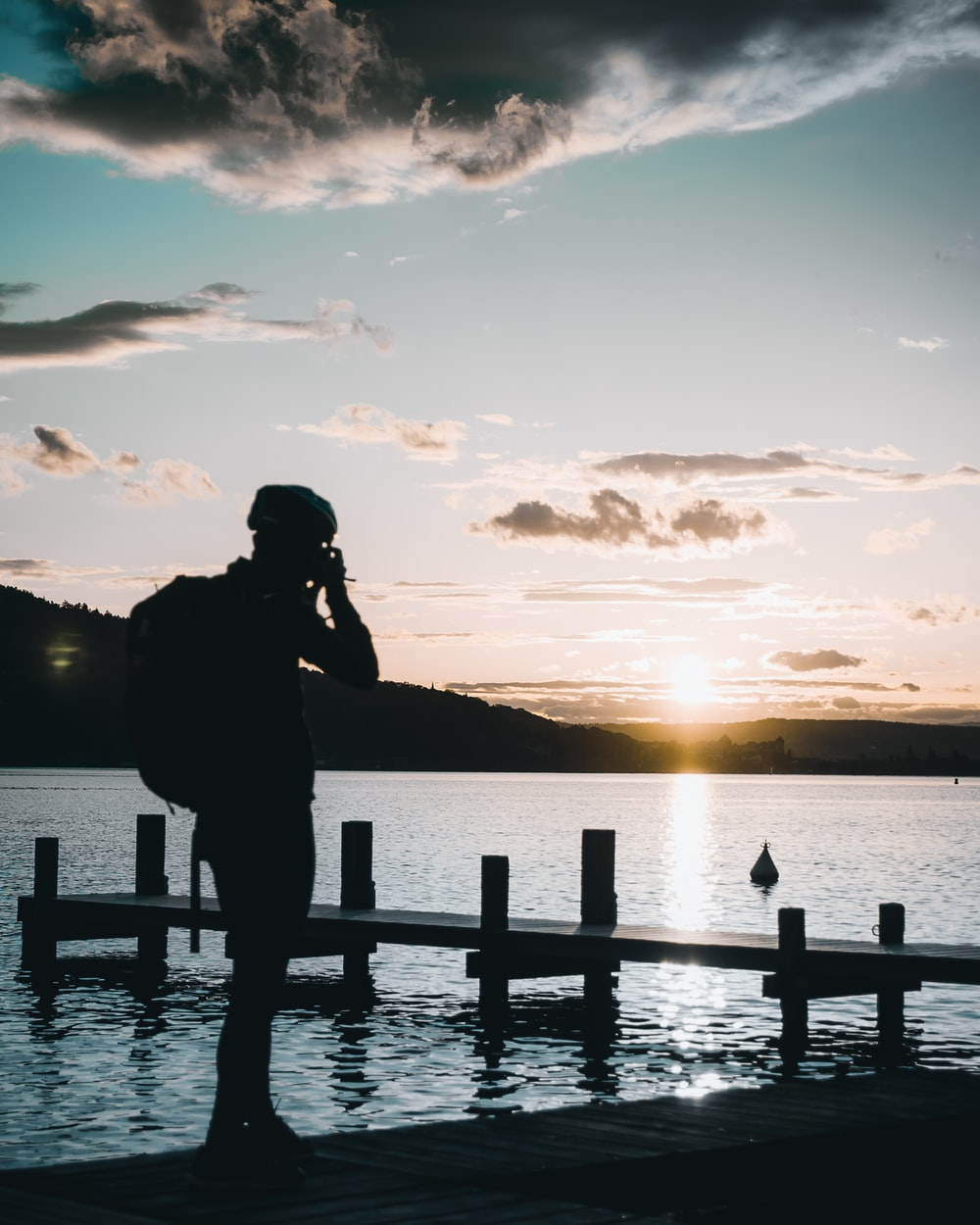 silhouette of person standing near dock during daytime