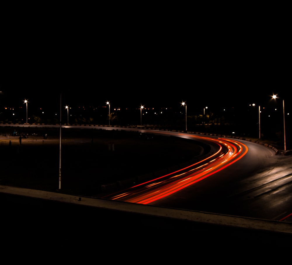 time lapse photography of road with red lights at night