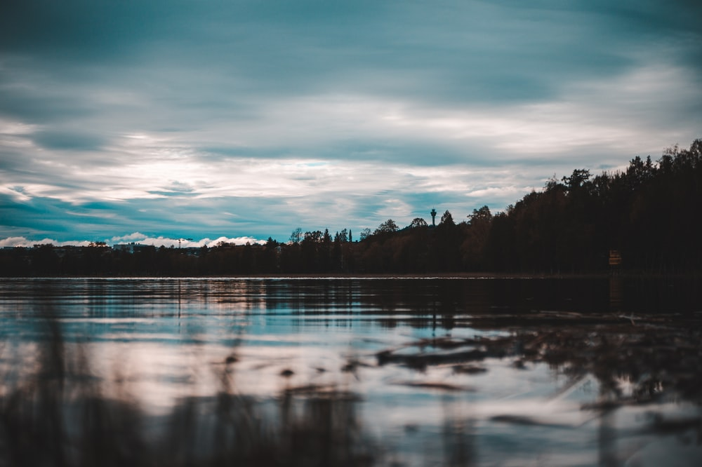shallow focus photo of body of water under cloudy sky during daytime