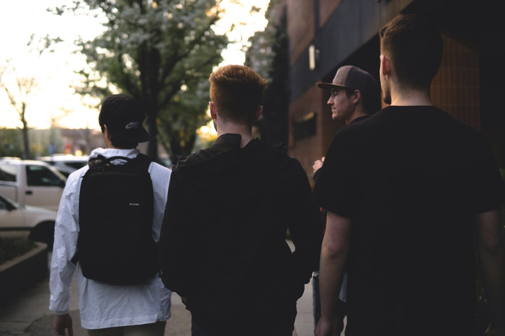 four men standing near cars
