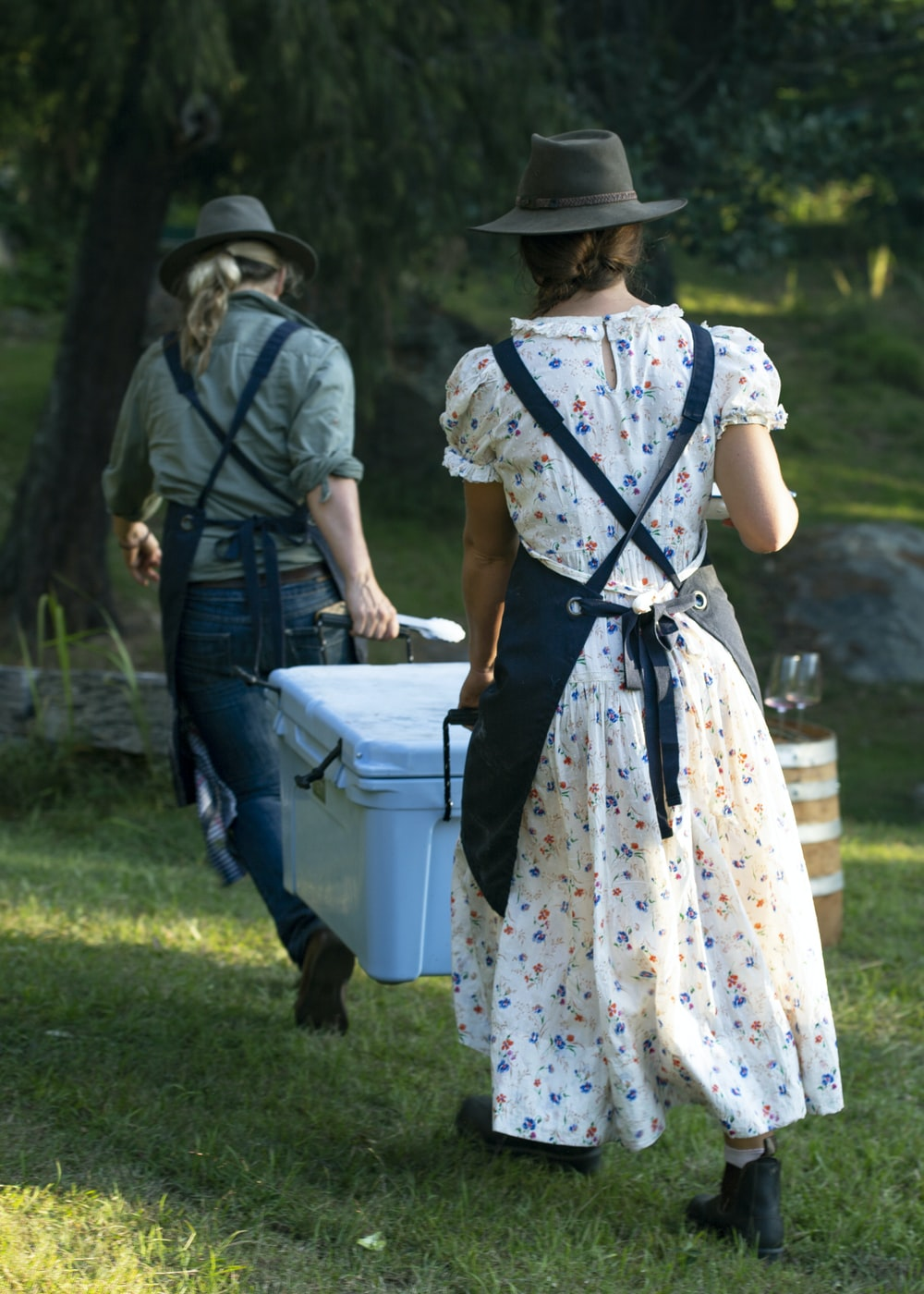 two women walking and carrying white cooler box on green field