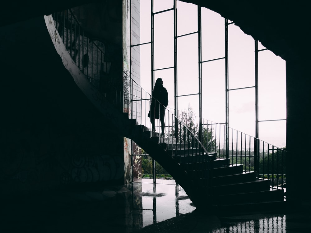 grayscale photography of woman on stair