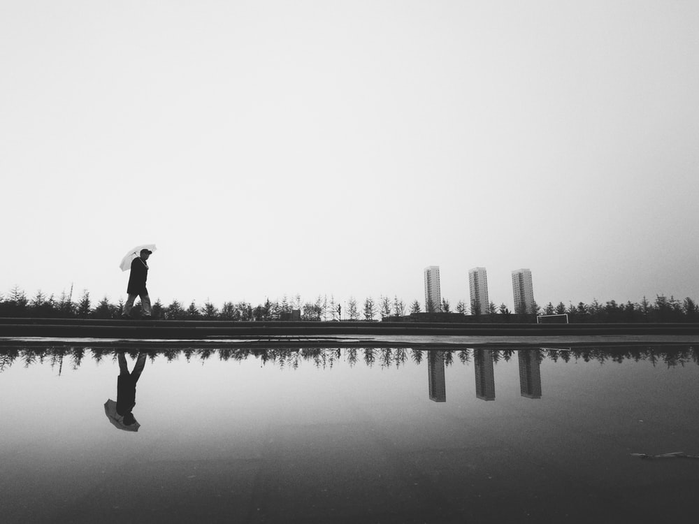 silhouette photography of man holding umbrella beside body of water