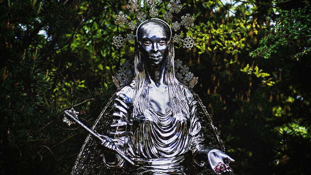 woman holding wand statue