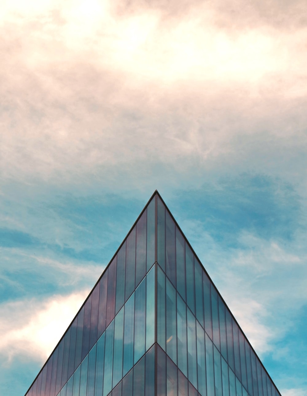 blue and gray glass walled building under white and blue skies