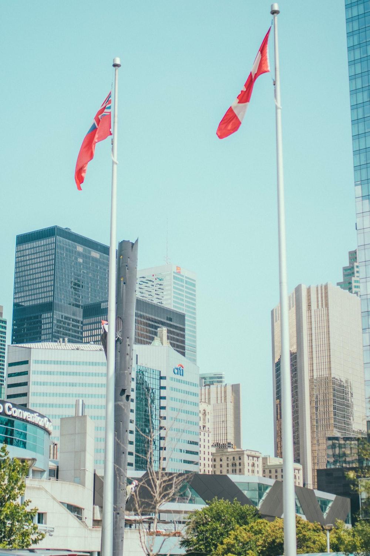 Canada flag waving on sky near high-rise buildings