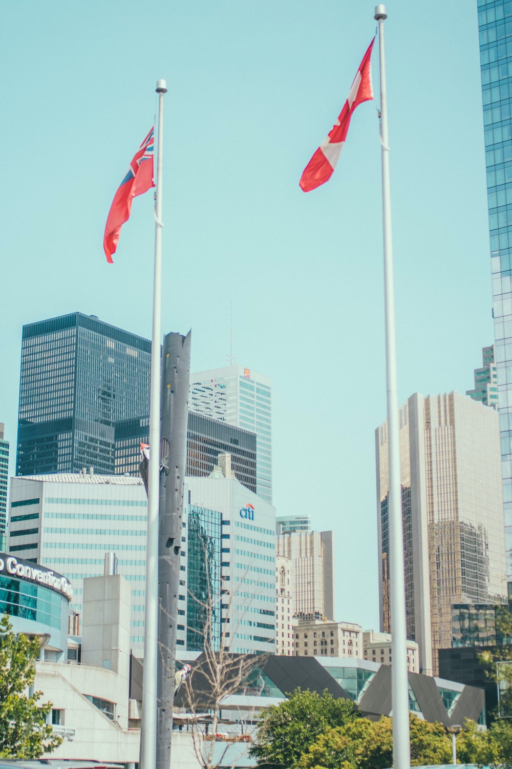 Canada flag waving on sky near high-rise buildings