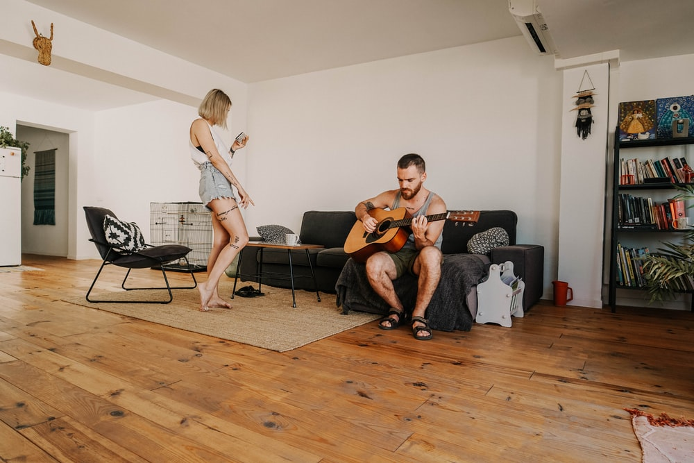 man playing guitar sitting on sectional sofa near standing woman