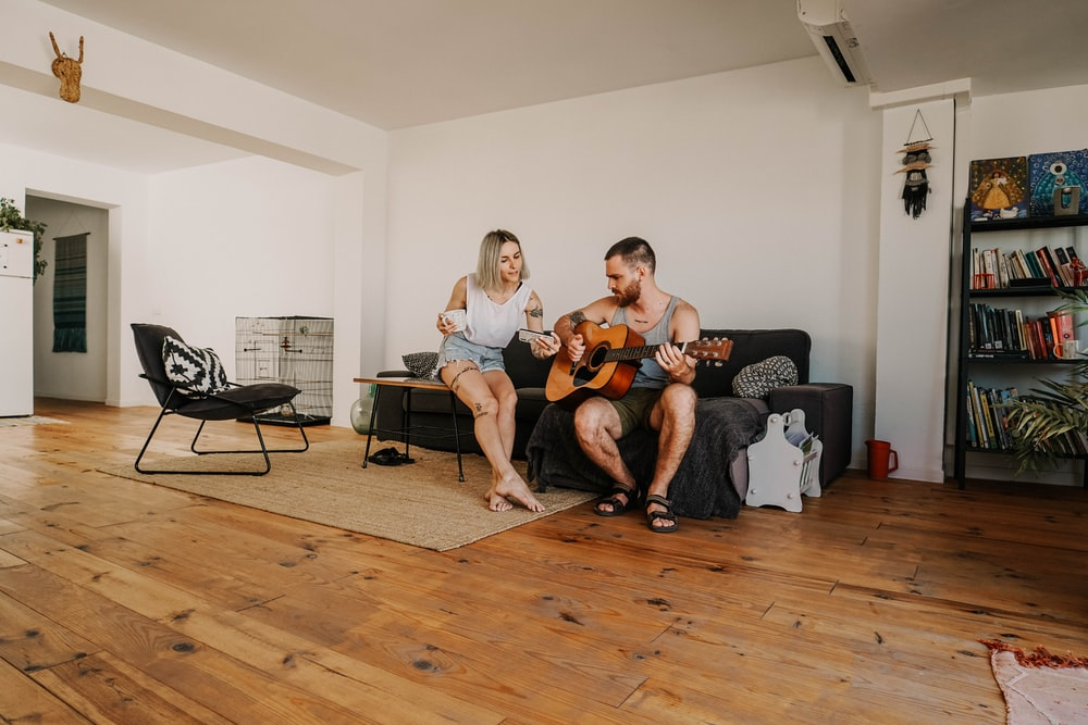 man sitting and playing acoustic guitar near woman in living room