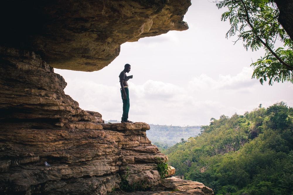 man standing on boulder