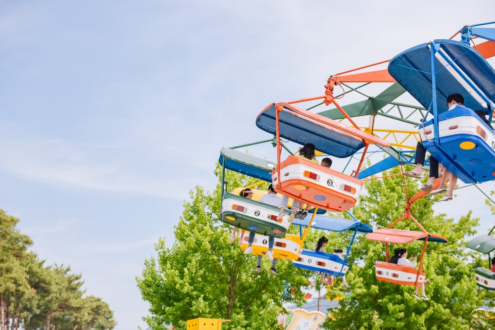 people riding carnival ride during daytime