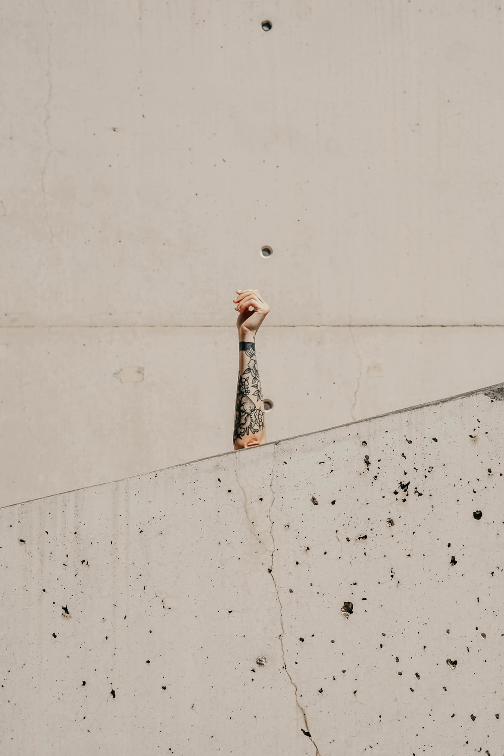 person's hand on front of gray wall