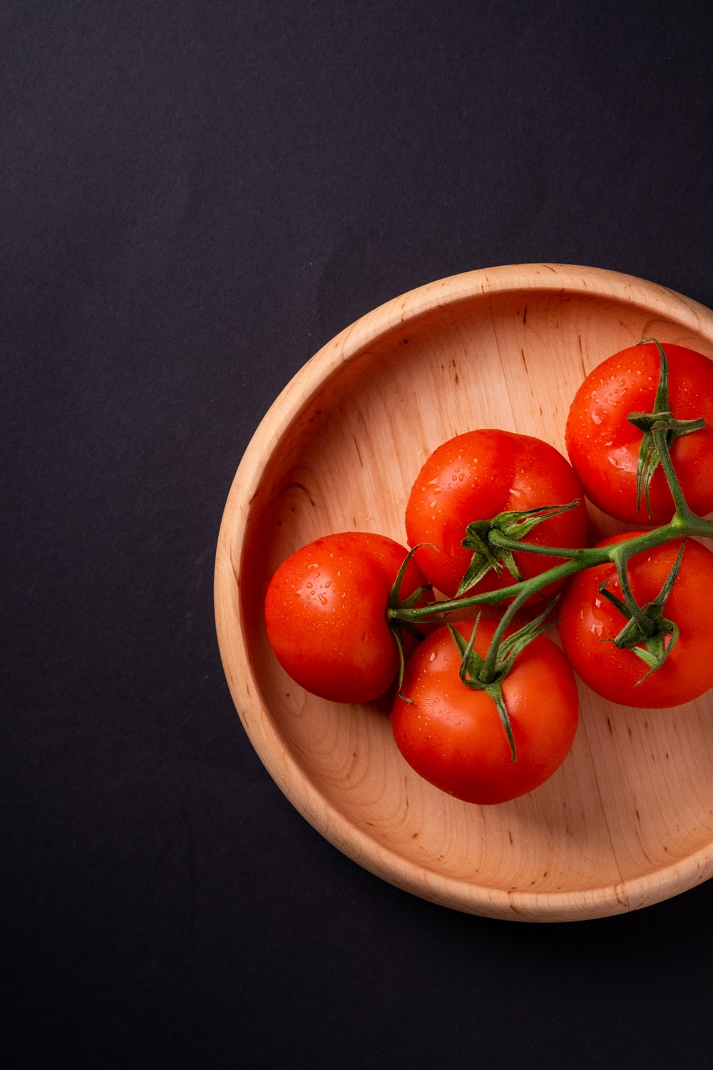five tomatoes in round brown wooden platet